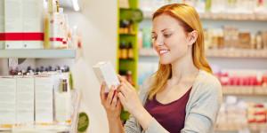 Frau schaut sich Packung von Pflegeprodukt an