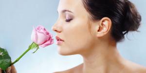 Frau riecht mit geschlossenen Augen an Rose