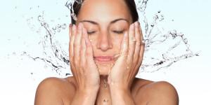 Frau wäscht sich das Gesicht mit Wasser