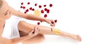 Frau bekommt Haarentfernungswachs auf das Bein aufgetragen