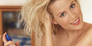 Frau sprüht Haarpflegemittel in Haar