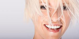 Lachende Frau mit weiß gefärbten, ins Gesicht hängenden, Haaren