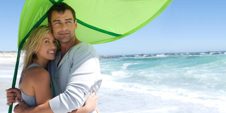 Paar umarmt sich unter Sonnenschirm am Strand
