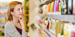 Frau steht nachdenklich vor Produktregal