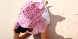 Frau mit Sonnenhut sonnt sich am Strand