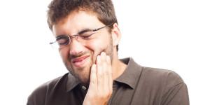 Mann hält sich die Wange vor Zahnschmerzen